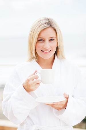 happy young woman in bathrobe drinking coffee in the morning photo