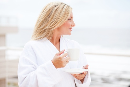 beautiful young woman in bathrobe drinking coffee in the morning photo