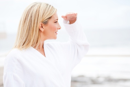 attractive young woman in bathrobe looking into distance in the morning  photo