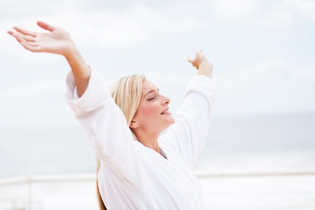 cute young woman in bathrobe with her arms opened in the morning photo