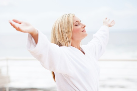 pretty young woman in bathrobe with arms opened in the morning Stock Photo - 12725482