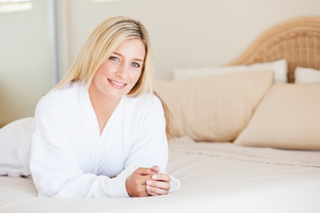 pretty young woman in bathrobe lying on bed photo