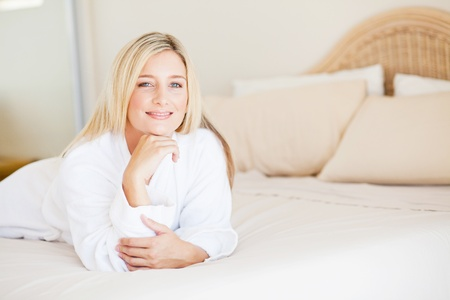 pretty young woman in pajamas lying on bed photo