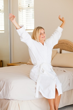 pretty young woman in pajamas just wake up and stretch on bed photo