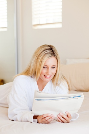 attractive young woman reading newspaper on bed photo