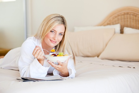 healthy young woman eating fruit salad on bed photo