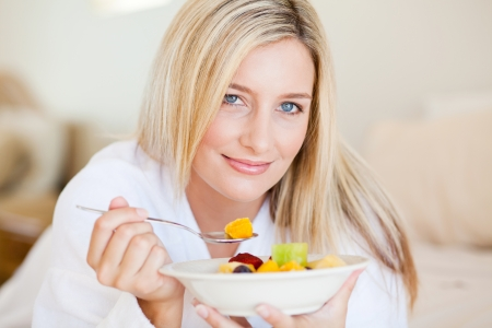 closeup of young attractive woman eating fruit salad on bed photo