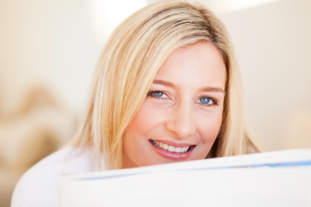happy young woman reading newspaper photo