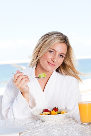pretty young woman eating breakfast with sea view in background photo