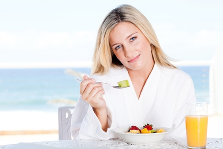 attractive young woman eating healthy breakfast, background is sea view photo