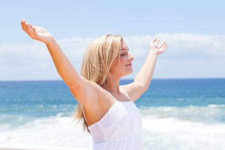 carefree young woman with arms open on beach Stock Photo