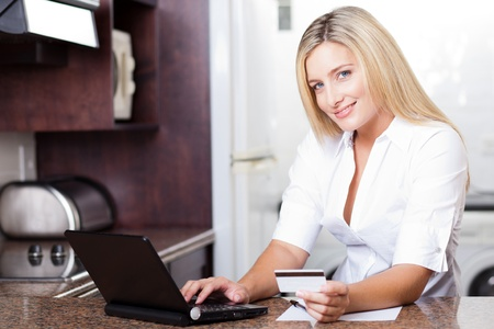 cute young blonde woman paying with credit card photo