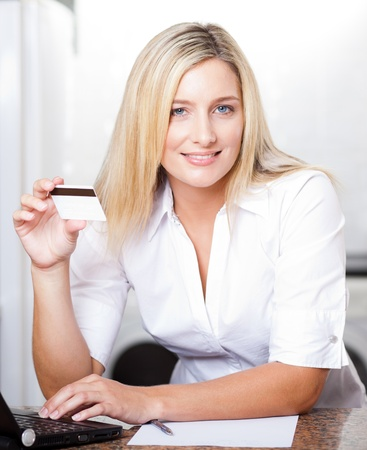 beautiful young blonde woman holding credit card photo