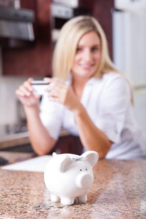 young woman saving money, focus on piggybank photo