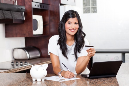 paying: beautiful young indian woman paying credit cards bills Stock Photo
