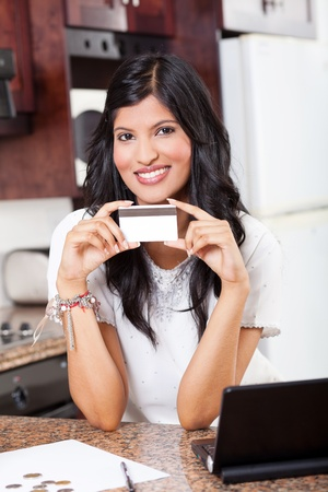 beautiful young indian woman holding credit card  photo