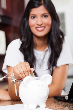 beautiful young indian woman putting a coin in piggy bank, focus on foreground photo