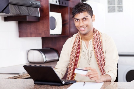 young handsome indian man holding credit card while using laptop computer at home photo