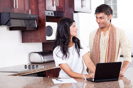 beautiful young indian couple using laptop at home photo