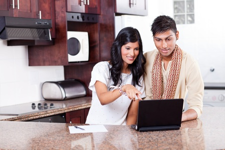 ethnic attire: young indian couple using computer at home