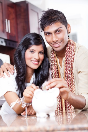 beautiful indian couple putting coins in piggybank photo