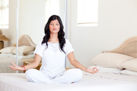 beautiful young woman practicing yoga meditation on her bed photo