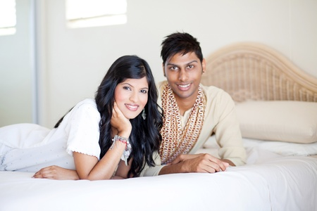 young indian couple lying on bed photo