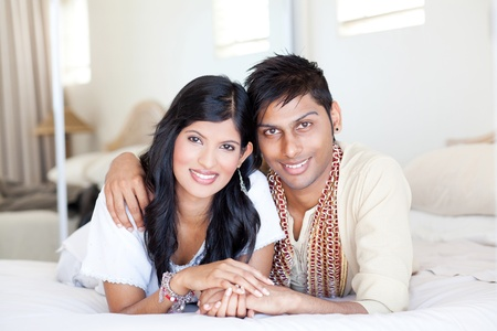 loving young indian couple in traditional clothing and lying on bed photo
