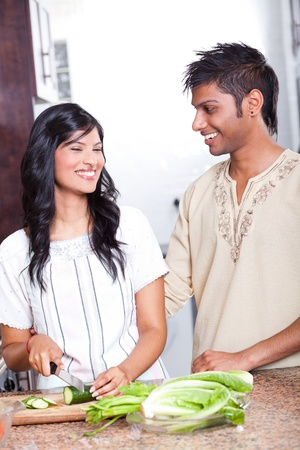 happy indian couple cooking in kitchen photo