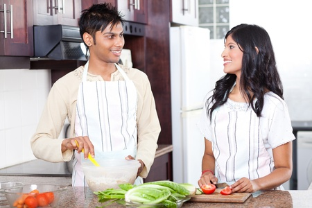 young indian couple cooking in modern kitchen photo