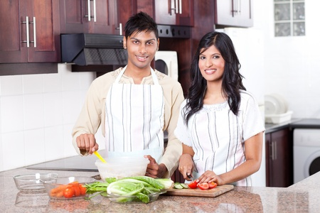 young indian couple cooking in kitchen  photo