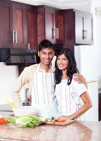 happy young indian couple hugging in kitchen photo