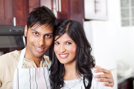 closeup portrait of young indian couple in kitchen with apron photo