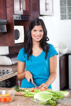 indian blue: young indian woman cooking in kitchen