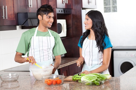 modern young indian couple cooking in kitchen photo