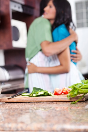 young couple hugging in kitchen, focus on foreground photo