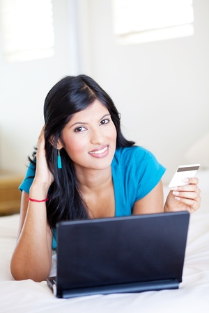 pretty young woman holding credit card on her bed Stock Photo - 12726004