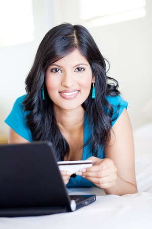 happy young woman holding credit card in front of computer Stock Photo - 12728074