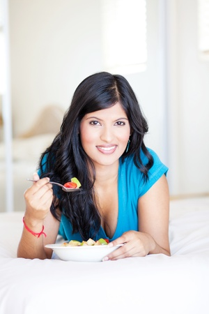attractive young woman eating fruit salad on bed photo