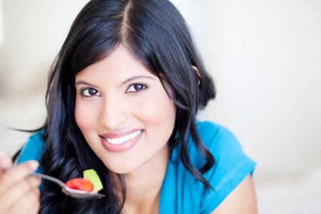 attractive healthy young woman eating fruit salad photo