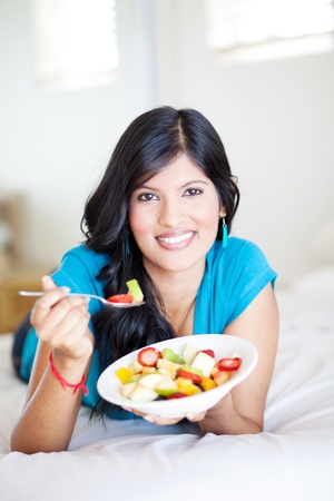 cheerful young woman eating fruit salad on bed photo