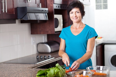 blue white kitchen: attractive middle aged woman cooking in kitchen Stock Photo