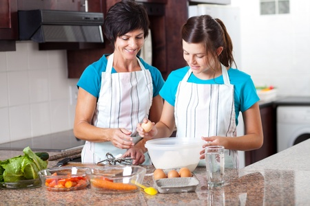 middle aged mother teaching teen daughter baking in kitchen photo