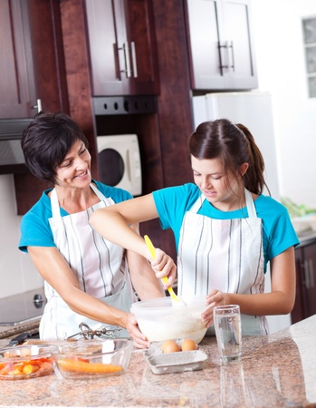 mother teaching teen daughter baking in kitchen photo