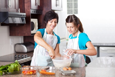 teen daughter helping mother baking in kitchen photo