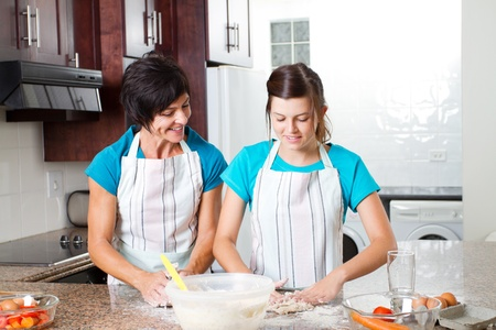 middle aged mother and teen daughter baking in kitchen photo
