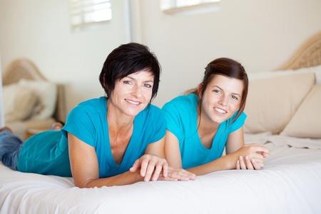 madre e hija adolescente: la madre de mediana edad y una hija adolescente acostado en la cama relajarse