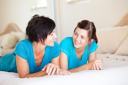 madre e hija adolescente: la madre de mediana edad y su hija adolescente en el chat en la cama