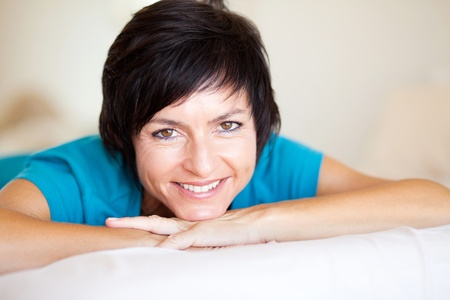 beautiful middle aged woman: cheerful middle aged woman lying on bed Stock Photo