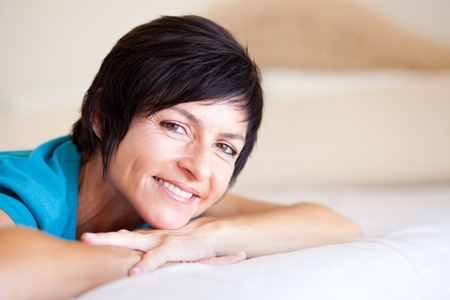 mature brunette: smiling middle aged woman lying on bed relaxing  Stock Photo